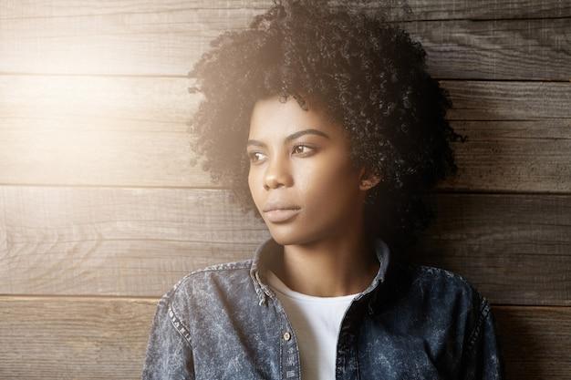 Headshot van modieuze jonge donkere vrouw met afro kapsel gekleed in denim jasje