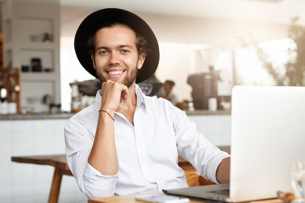Headshot van modieuze jongeman met laptopcomputer, met behulp van snelle internetverbinding tijdens de lunch in het interieur van het gezellige café.