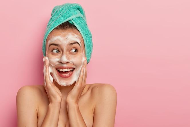 Headshot van mooi glimlachend vrouwelijk model raakt wangen, kijkt opzij, wast gezicht met zeepbel, heeft naakt lichaam, draagt turquoise zachte handdoek op hoofd, poseert over roze muur, kopieer ruimte voor promotie