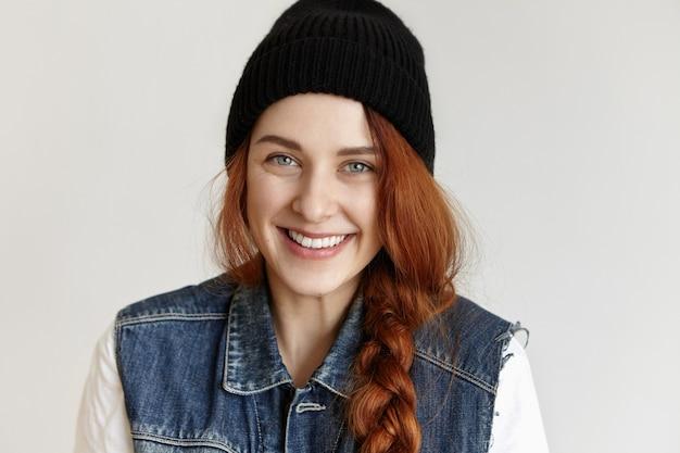 Headshot van mooi meisje in stijlvolle kleding, glimlachend vreugdevol genieten van gelukkig tienerleven