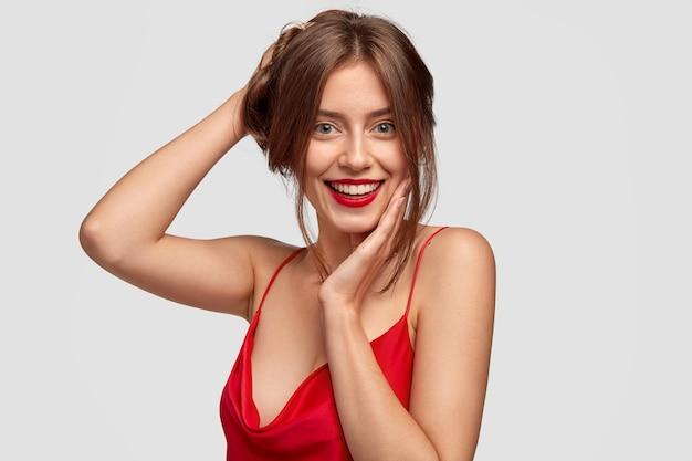 Headshot van mooi vrouwelijk model heeft een gezonde huid, positieve uitdrukking
