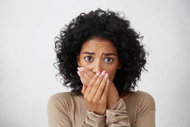 Headshot van mooie, angstige jonge europese vrouw met donkere huidskleur en krullend kapsel die haar mond sluit om niet te schreeuwen, zich angstig en doodsbang voelt, haar ogen en kijkt vol angst en angst