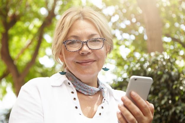 Headshot van mooie blanke vrouwelijke gepensioneerde op zoek met vrolijke, vrolijke uitdrukking terwijl ze mobiele telefoon gebruikt om online te communiceren met haar vrienden, nieuws te lezen, foto's te verzenden