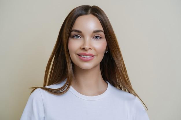 Headshot van mooie donkere haired jonge europese vrouw kijkt met tedere uitdrukking, heeft vriendschappelijke houding, praat terloops met vrienden, draagt casual witte t-shirt ,.