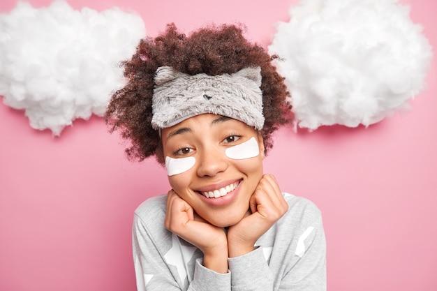 Headshot van mooie glimlachende vrouw houdt handen onder kin kijkt vrolijk naar camera draagt slaapmasker en pyjama geniet van goedemorgen past schoonheidspatches toe onder ogen geïsoleerd over roze studiomuur