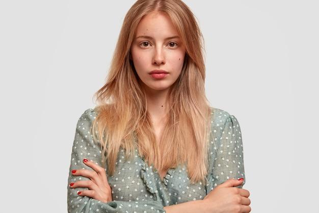 Headshot van mooie jonge vrouw met aantrekkelijk uiterlijk, houdt armen gevouwen, gekleed in modieuze blouse