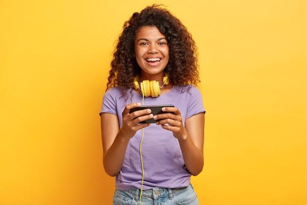 Headshot van mooie jonge vrouw met afrokapsel poseren tegen de gele muur