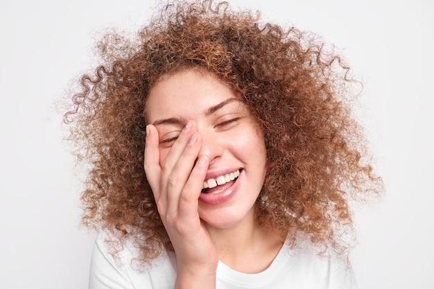 Headshot van mooie oprechte europese vrouw met krullend borstelig haar heeft plezier lacht uit dekt gezicht met palmen glimlacht in grote lijnen geluk geïsoleerd over witte muur. positieve emoties