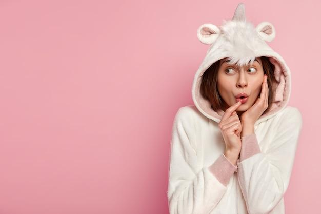 Headshot van mooie verrast schattige jonge vrouw kijkt weg, heeft wijd geopende ogen, draagt zacht kigurumi-kostuum met capuchon, geïsoleerd over roze muur, vrije ruimte voor uw promotionele inhoud.