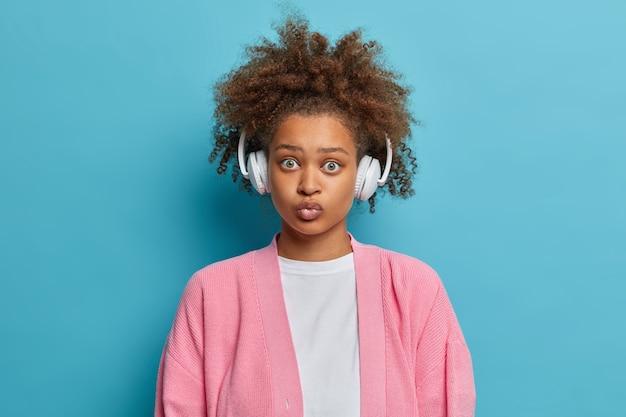 Headshot van mooie verrast vrouw met krullend borstelig haar draagt grote koptelefoon op oren houdt lippen afgerond luistert favoriete liedjes gekleed in casual trui.