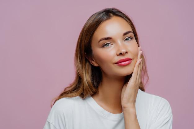 Headshot van mooie vrouwelijke model raakt zacht wang, geniet van delicate gezichtshuid