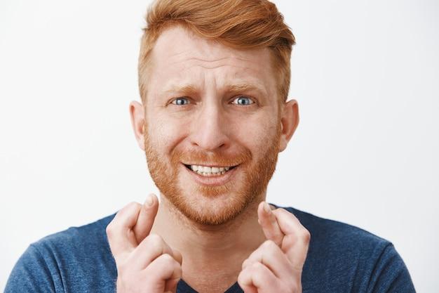 Headshot van nerveuze paniekerige knappe man met rood haar en borstelharen, fronsende gebalde tanden en gekruiste vingers voor geluk
