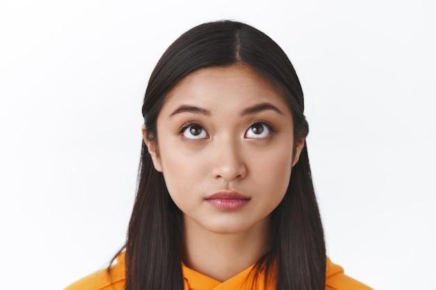 Headshot van nieuwsgierig schattig aziatisch meisje met kort donker haar dat omhoog kijkt, iets interessants naar boven observeert, intrigerende scène denkt of overweegt, staande witte muur