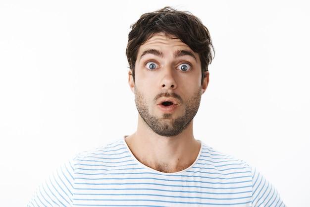 Headshot van onder de indruk sprakeloze en verbaasde knappe man met borstelharen en blauwe ogen die wauw zeggen, hijgend met open mond wijd open ogen aan de voorkant in shock en verbazing