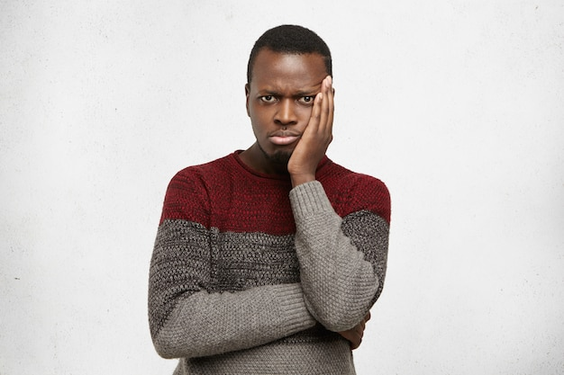 Headshot van ongelukkig gefrustreerd jong zwart mannetje dat in verwarring gebrachte uitdrukking heeft, hand op zijn wang houdt en armen gevouwen houdt. triest afro-amerikaanse man gekleed in trui gevoel vervelen of depressief
