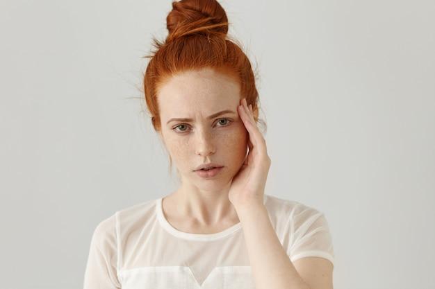 Headshot van ongelukkige jonge roodharige vrouw met gefrustreerde en pijnlijke gezichtsuitdrukking, fronsen, tempel met hand aanraken, lijden aan slechte hoofdpijn of migraine terwijl ze geconfronteerd wordt met stress op het werk