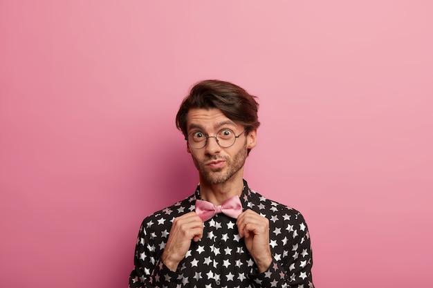 Headshot van ongeschoren man past roze bowtie aan, heeft een elegante uitstraling, draagt een zwart shirt met sterrenprint, kijkt door een ronde bril