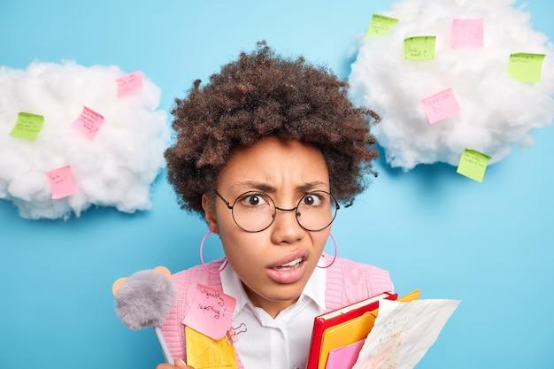 Headshot van ontevreden afro-amerikaans schoolmeisje houdt kleurrijke mappen vast met papieren portemonnees lippen kijkt ontevredenheid vondsten over nog een taak voorbereidt projectwerk poses rond kleurrijke stickers