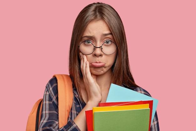 Headshot van ontevreden schoolmeisje portemonnees lippen met aanstootgevende blik, heeft droevige uitdrukking, draagt een ronde bril, draagt een rugzak