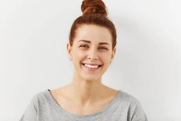 Headshot van ontspannen jonge gember vrouwelijke hipster met perfecte mooie glimlach op zoek met gelukkige uitdrukking