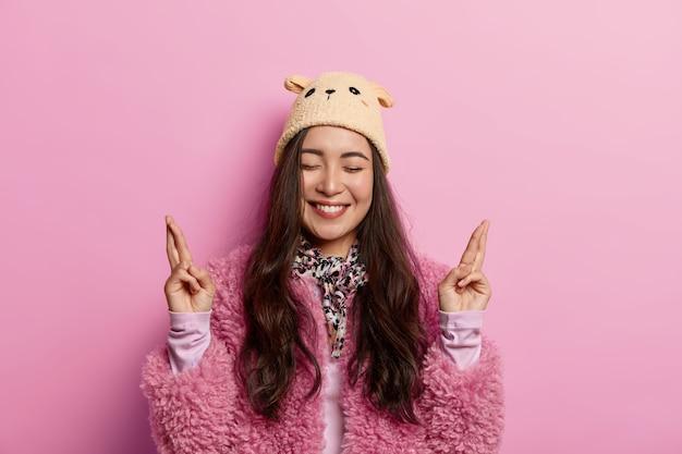 Headshot van oprechte mooie vrouw kruist vingers voor geluk, doet wensen en glimlacht wijd, heeft een dolgelukkige uitdrukking, gelooft in fortuin