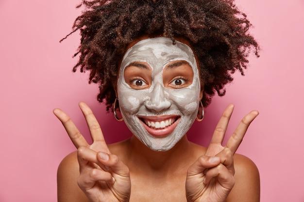 Headshot van optimistische vrouw heeft vreugde terwijl ze kleimasker aanbrengt, vredesgebaar maakt met beide handen met blote schouders, wil een frisse, gezonde huid hebben, geïsoleerd over roze muur