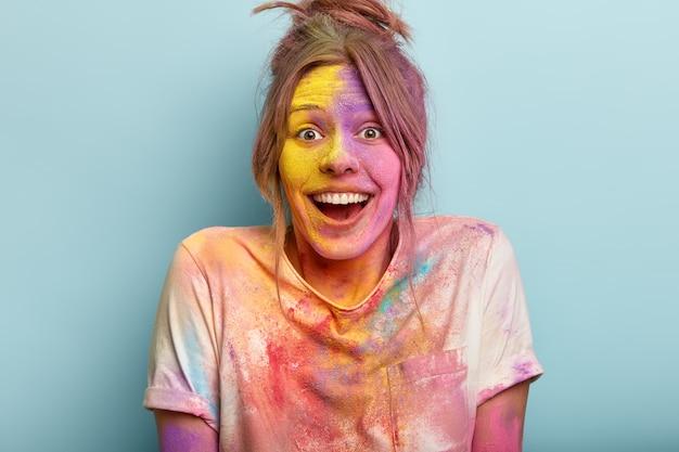 Headshot van optimistische vrouw speelt met kleuren op holi-festival, gekleed in wit t-shirt