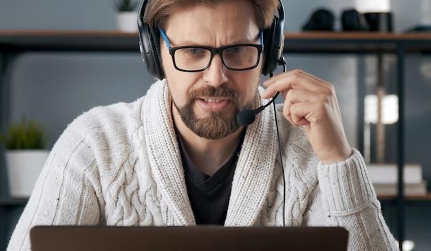 Headshot van plichtsgetrouwe man met hoofdtelefoon doen afstandswerk kijken naar computerscherm, lockdown