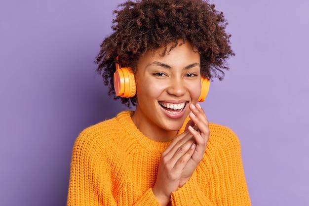 Headshot van positieve donkere vrouw luistert muziek in stereo draadloze koptelefoon lacht uit en houdt handen bij elkaar draagt casual trui