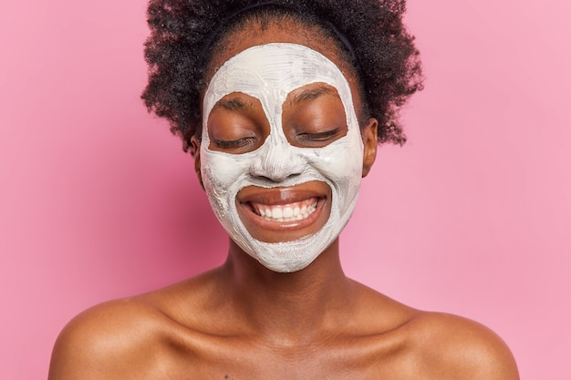 Headshot van positieve vrouw glimlacht breed draagt wit gezichtsmasker om poriën te verminderen en fijne lijntjes ondergaat schoonheidsprocedures poseert topless tegen roze muur toont witte tanden