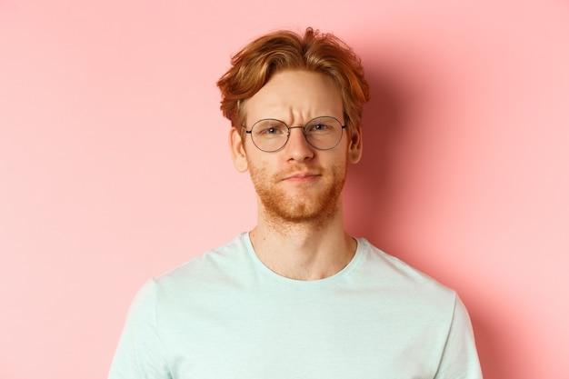 Headshot van sceptische roodharige man met bril en t-shirt fronsend teleurgesteld starend met afkeur...