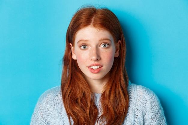 Headshot van schattig roodharige meisje met sproeten, hoopvol en onschuldig op zoek naar camera, staande op blauwe achtergrond.