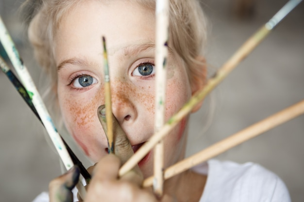 Headshot van schattig vrouwelijk blond kind, met borstels in haar hand, kijken en glimlachen. schattig klein meisje met blond haar en blauwe ogen in witte doek. gelukkig jeugdconcept