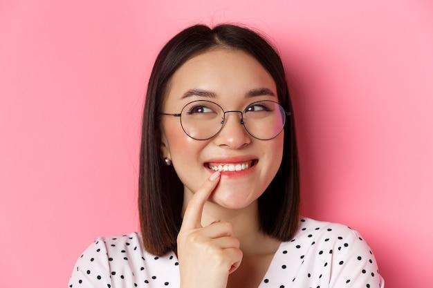 Headshot van schattige aziatische vrouw in trendy bril die lacht, een idee heeft, denkt en kijkt naar de linkerbovenhoek, roze achtergrond.