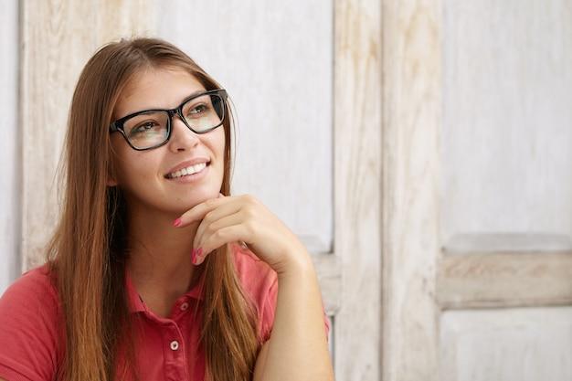 Headshot van schattige jonge vrouw, gekleed in poloshirt en rechthoekige bril, hand op haar kin te houden terwijl ze aan iets aangenaams denkt, glimlachend