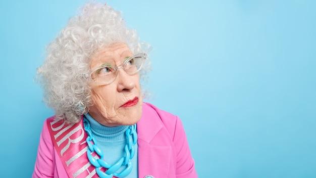Headshot van senior vrouw met krullend haar, geconcentreerd opzij, heeft een doordachte uitdrukking, gerimpeld gezicht draagt een bril voor goed zicht draagt feestelijke kleding