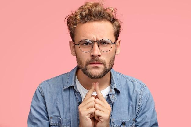 Headshot van serieuze intelligente jongeman luistert iets met een oplettende blik, heeft een nauwgezette blik
