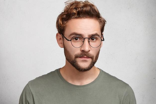 Headshot van serieuze slimme man professor die lezing gaat leiden, draagt een bril
