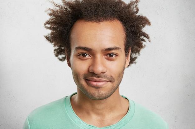 Headshot van stijlvolle hipster man met borstelige kapsel, stoppels, stralende ogen, poses