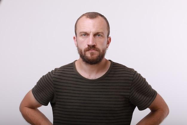 Headshot van stijlvolle man met baard, modieus kapsel oorbel in oor dragen