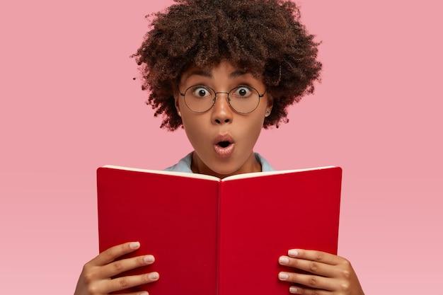 Headshot van stomverbaasde jonge vrouw met donkere huid opent mond van verbazing, houdt rood leerboek vast, verrast met onverwachte afloop van romantisch verhaal, modellen binnen over roze muur. omg-concept
