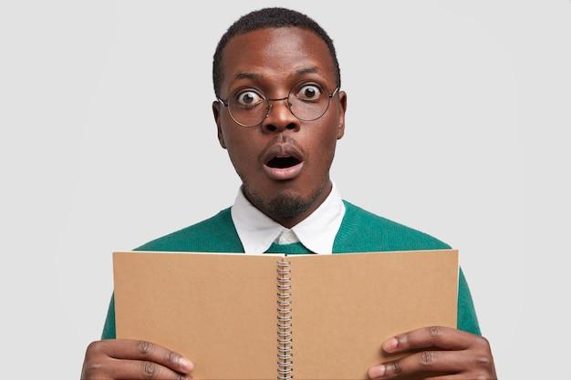 Headshot van stomverbaasde zwarte man houdt mond open, verbaasd over iets vreselijks, houdt geopend spiraalvormig notitieblok vast, heeft donkere huid