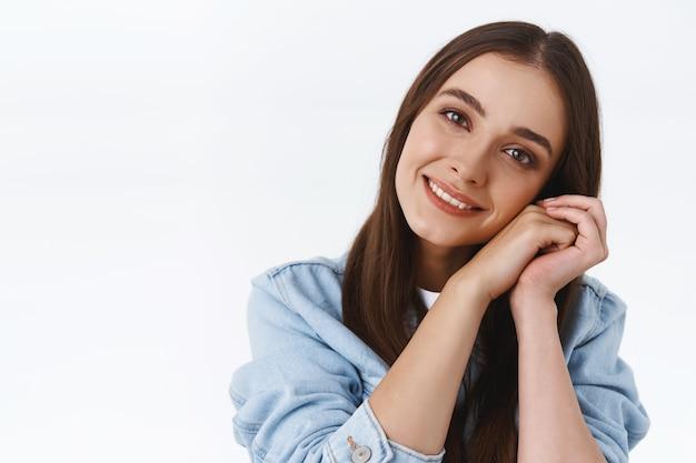 Headshot van tedere en vrouwelijke dromerige kokette vrouw in spijkerjasje, hoofd kantelen, handen in elkaar slaan in de buurt van de wang, glimlachend mooi met een tevreden romantische blik, staande witte achtergrond