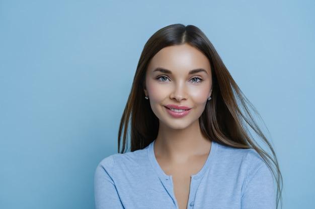 Headshot van tedere vriendin met een aangename uitstraling, glimlacht teder, regelt spa salon ontspanningsweekend, tevreden na cosmetische ingrepen, heeft een gezonde frisse huid, geïsoleerd op blauwe achtergrond