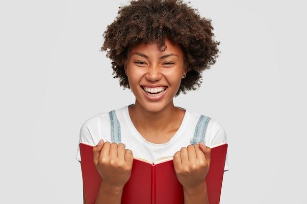 Headshot van tevreden donkere boekenwurm die graag de bestseller leest