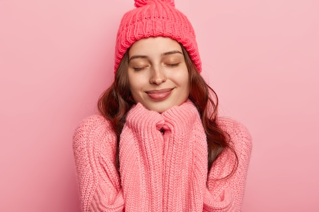 Headshot van tevreden europese vrouw heeft een gezonde huid, houdt de ogen dicht, handen onder de kin, draagt een warme muts en oversized trui, geïsoleerd op een roze achtergrond.