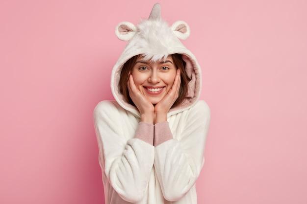 Headshot van tevreden lieftallige vrouw raakt wangen zachtjes aan, lacht vrolijk, gekleed in kigurumi-kostuum