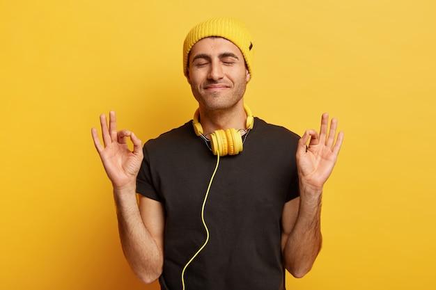 Headshot van tevreden mannelijk model maakt oke gebaar met beide handen, ogen gesloten, mediteert alleen binnenshuis