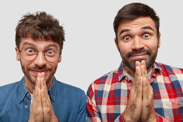 Headshot van tevreden twee mannen houden de handen tegen elkaar gedrukt