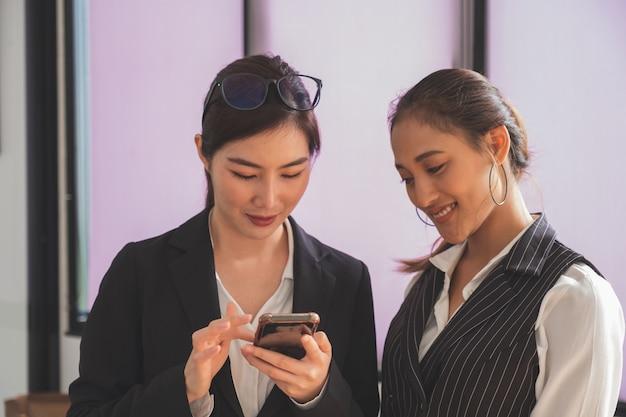Headshot van twee professionele aziatische vrouwen in zakelijke casual gebruiken en kijken op slimme telefoon